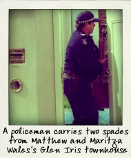 A policeman carries two spades from Matthew and Maritza Wales's Glen Iris townhouse-pola