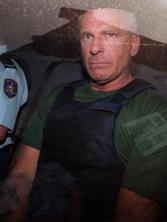 Criminal Arthur Neddy Smith leaves Waverley Local Court in Sydney in custody of prison officer and wearing a bulletproof vest