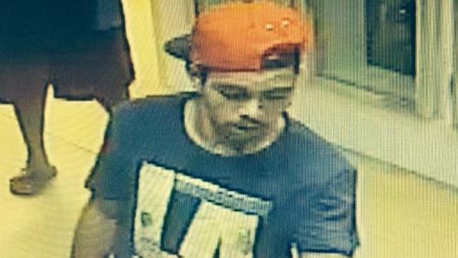 """CCTV from BP Cue petrol station showing escapee Cameron John Graham wearing orange cap and dark T shirt with """"LA"""" in large letters on the front."""