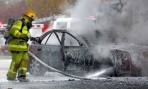 Firefighters hose down the car at the Safeway Caltex service station.