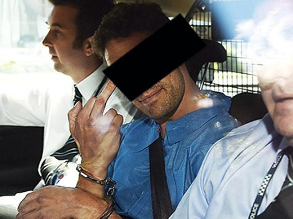 The man smiled at cameras and stuck up his finger as he was taken from Sunshine police station. Source: HeraldSun